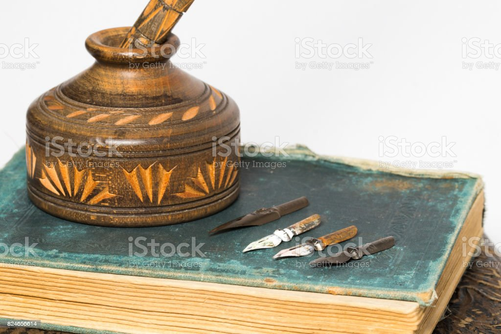 wooding ink pot with old books stock photo