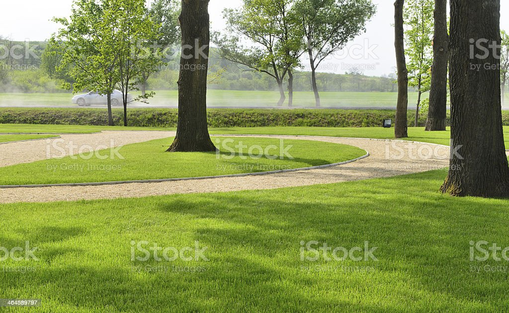 Woodland park with manicured lawns and a road royalty-free stock photo
