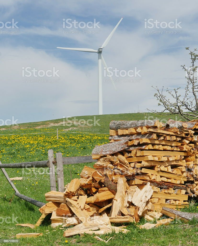 Woodpile with wind power station on background stock photo