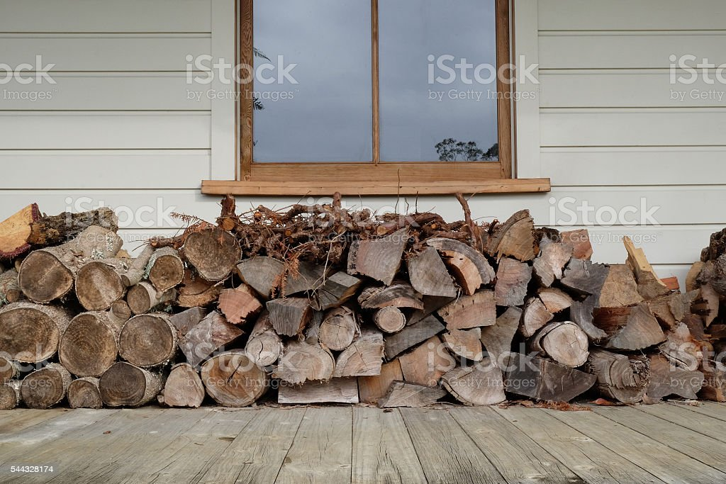 Woodstack under window on verandah stock photo