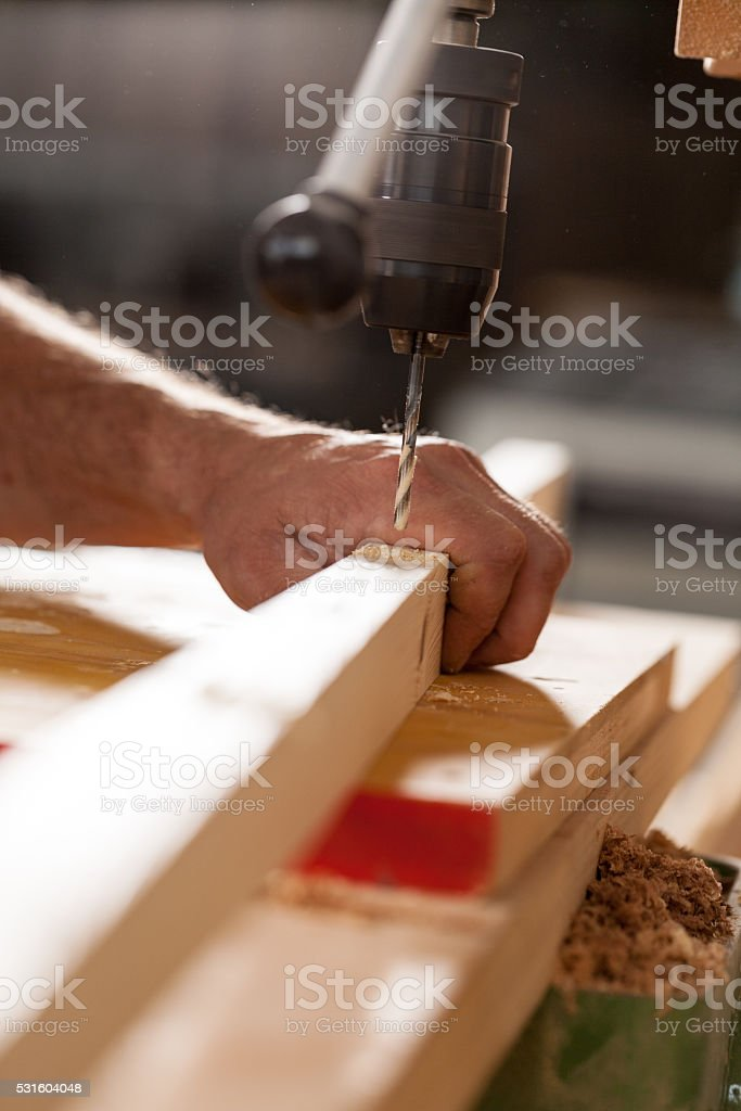 woodworker drilling a plank with machinery stock photo