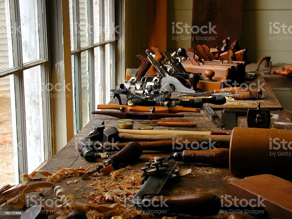 Woodworking tools and wood shavings on table near window royalty-free stock photo