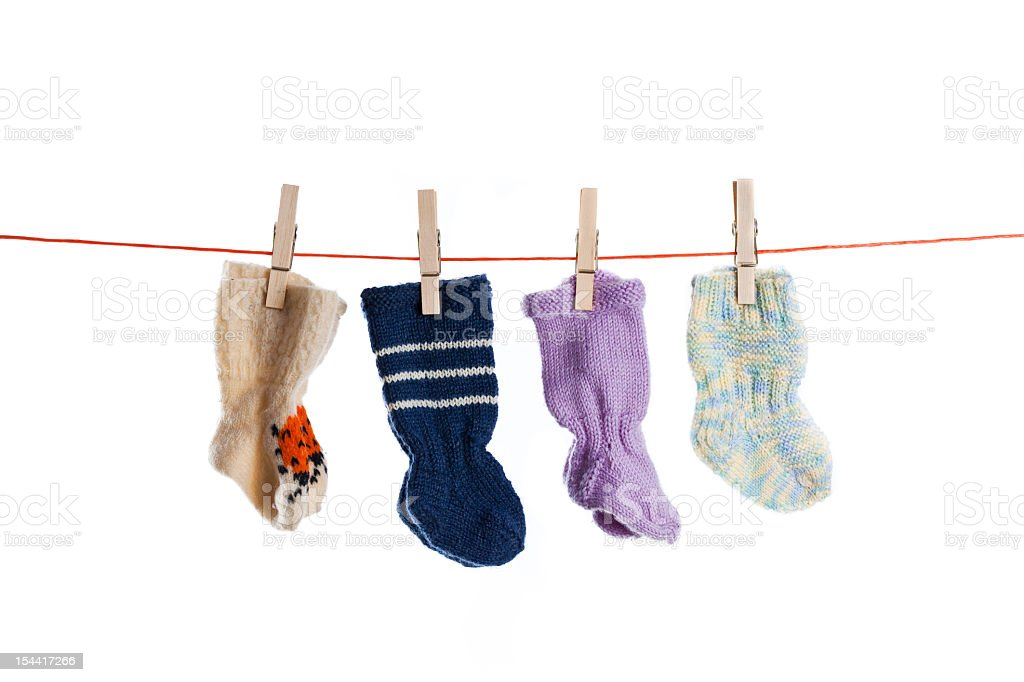 Wool baby socks hanging on clothesline with white background royalty-free stock photo