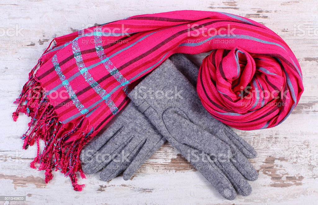 Woolen gloves and shawl for woman on old wooden background stock photo