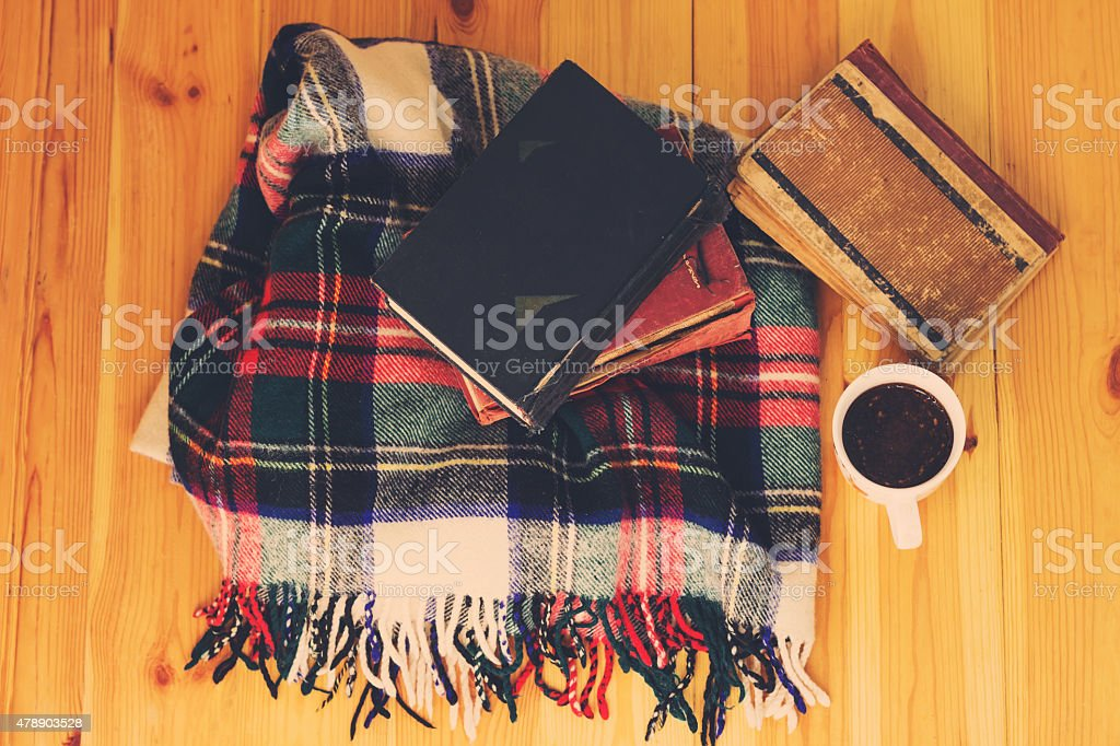 Woolen plaid, cup of coffee, old books on wooden background. stock photo