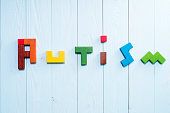 Word Autism built of colorful wooden blocks on wooden background