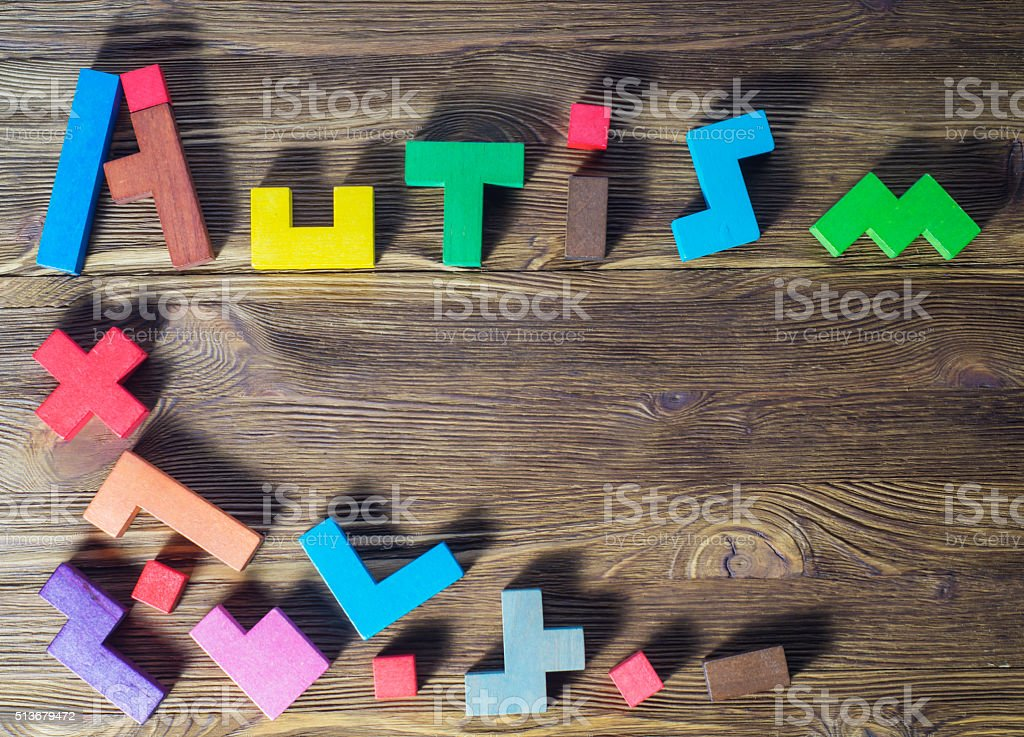 Word Autism built of wooden puzzles on a wooden background. stock photo