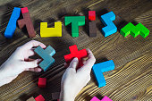 Word Autism built of wooden puzzles on a wooden background.