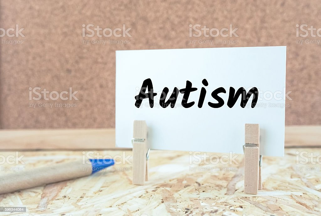 word autism on note paper wooden desk background stock photo