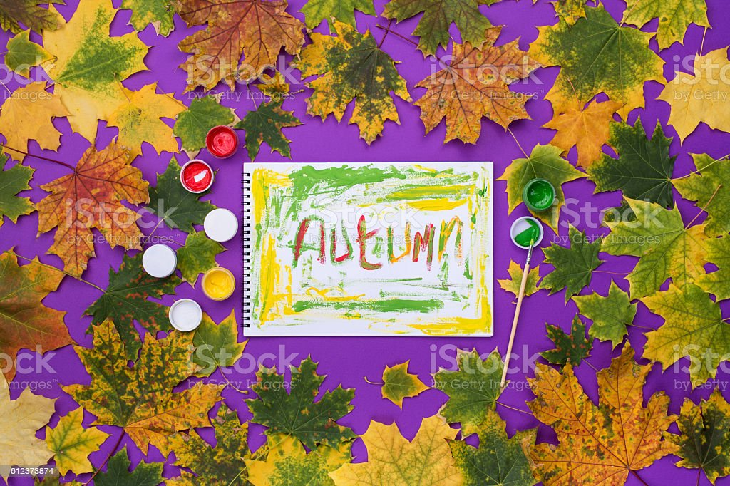 Word autumn, drawn by paints in an album stock photo