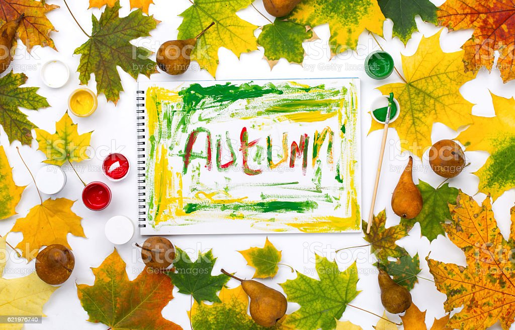 Word autumn in an album with autumn leaves and pear stock photo