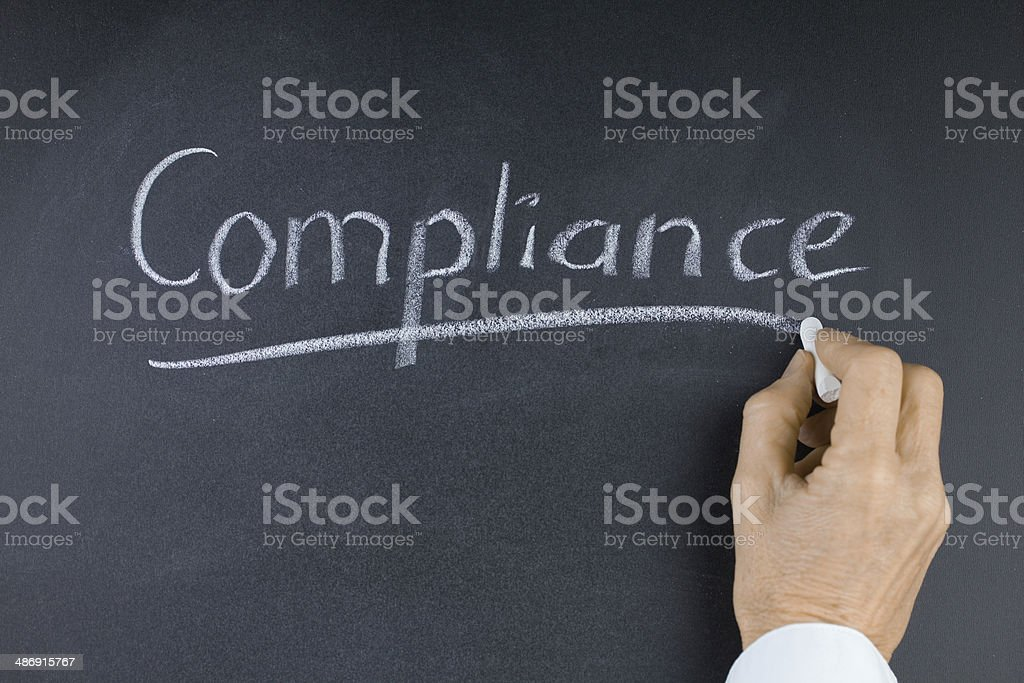 Word Compliance on Blackboard with Hand and Chalk stock photo