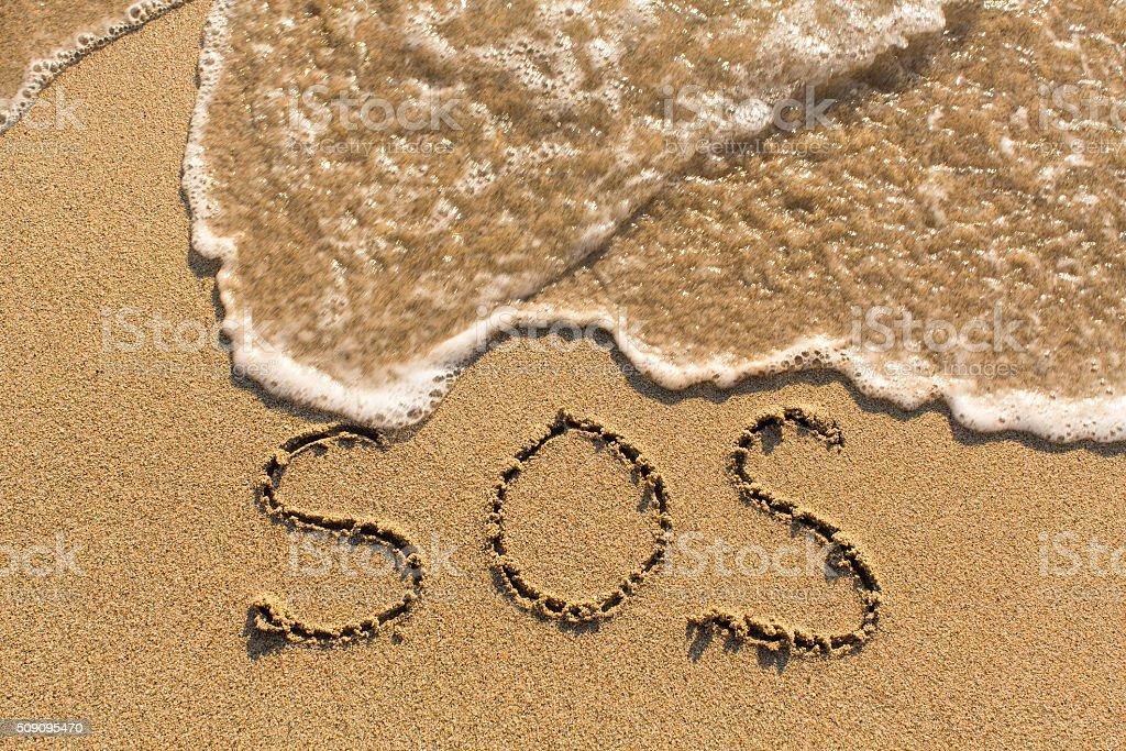 SOS - word drawn on the sand beach stock photo