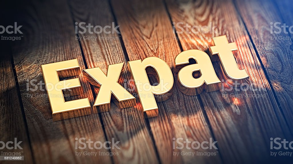 Word Expat on wood planks stock photo