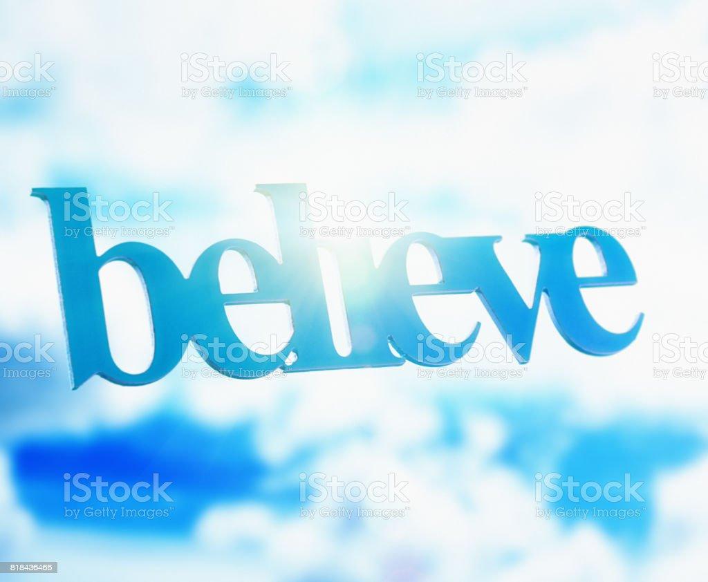 3D word floating in dreamy summer sky reads 'believe' stock photo