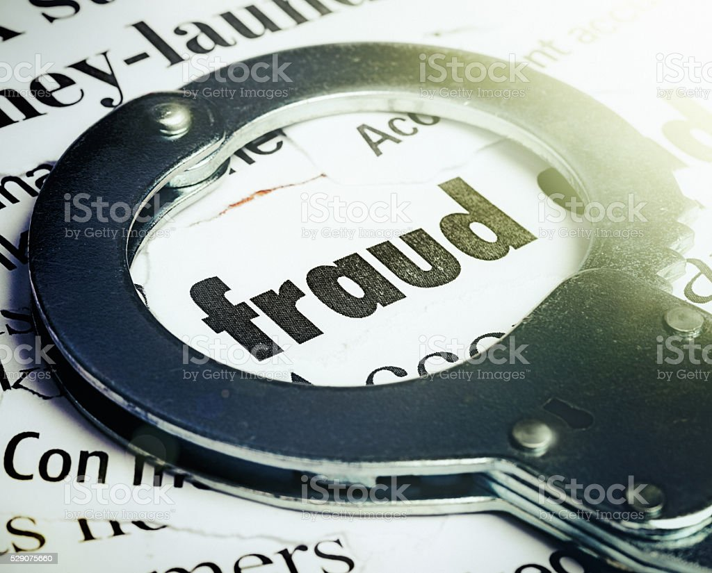Word 'fraud' encircled by handcuff; white-collar crime stock photo