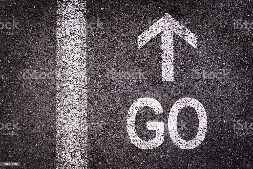 Word go and an arrow written on  asphalt stock photo