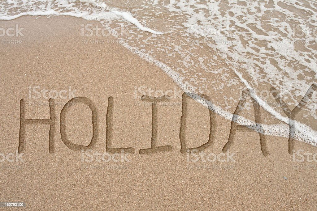 word holiday on sand Hand write royalty-free stock photo