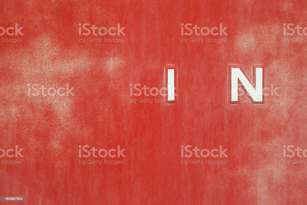 Word IN On Red Grunge Metal Background royalty-free stock photo