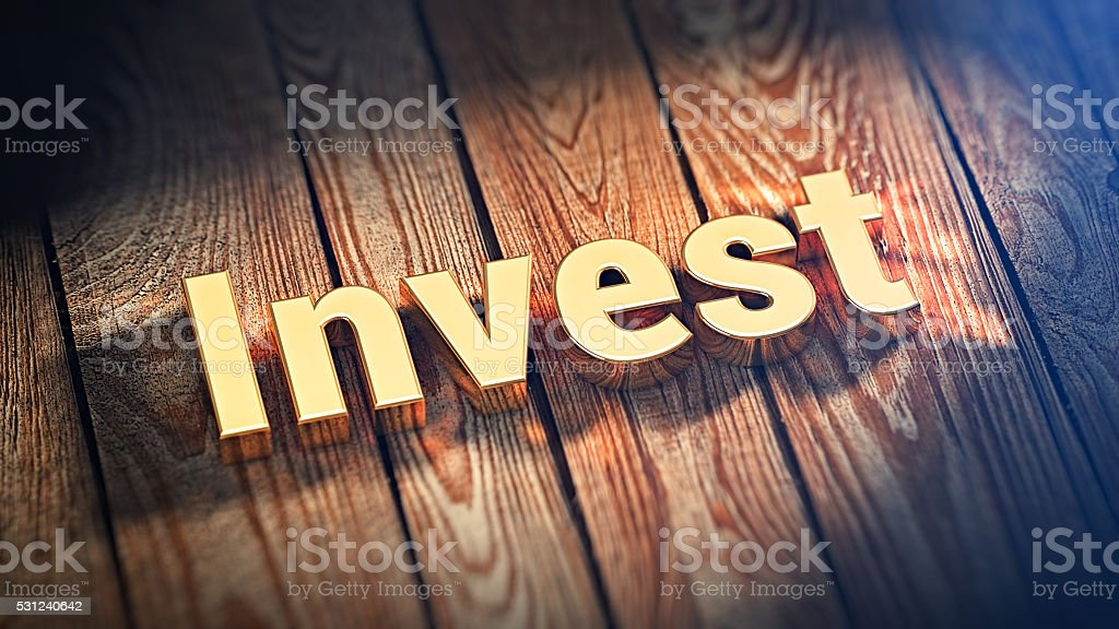 Word Invest on wood planks stock photo