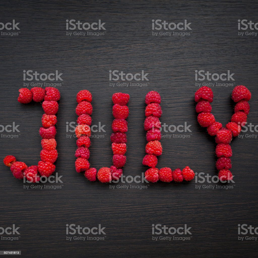 Word July of raspberries on table royalty-free stock photo