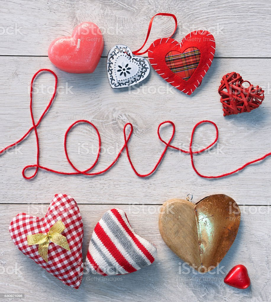 Word 'love' and different hearts on white wooden background stock photo