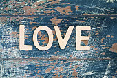 Word love written on rustic wooden surface