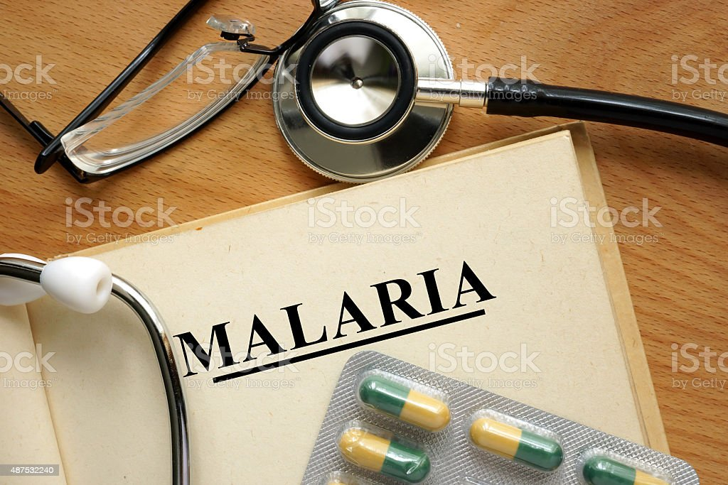 Word Malaria  on a paper and pills on the wooden table. stock photo