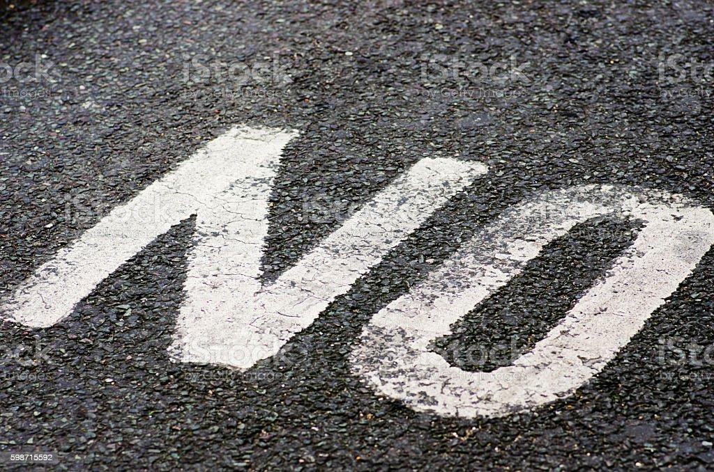 Word no white painted on black asphalt. stock photo