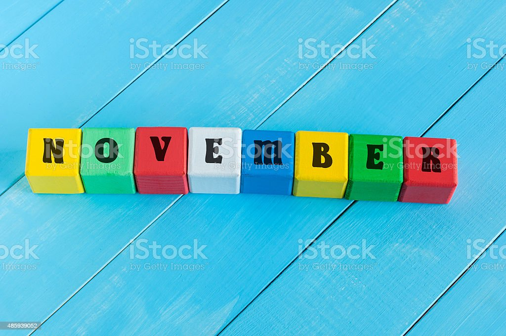 Word November on color wooden cubes with light blue wood stock photo