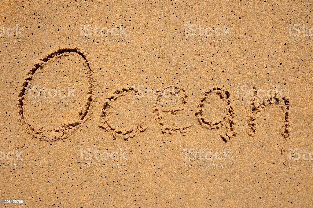 word ocean written in the sand stock photo