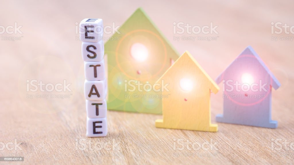 Estate Word Of Cube Letters Behind Coloured House Symbols With Light