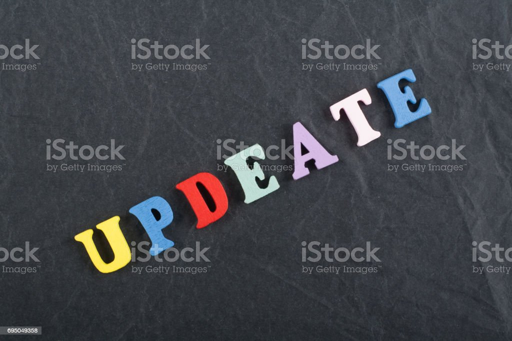 UPDEATE word on black board background composed from colorful abc alphabet block wooden letters, copy space for ad text. Learning english concept stock photo