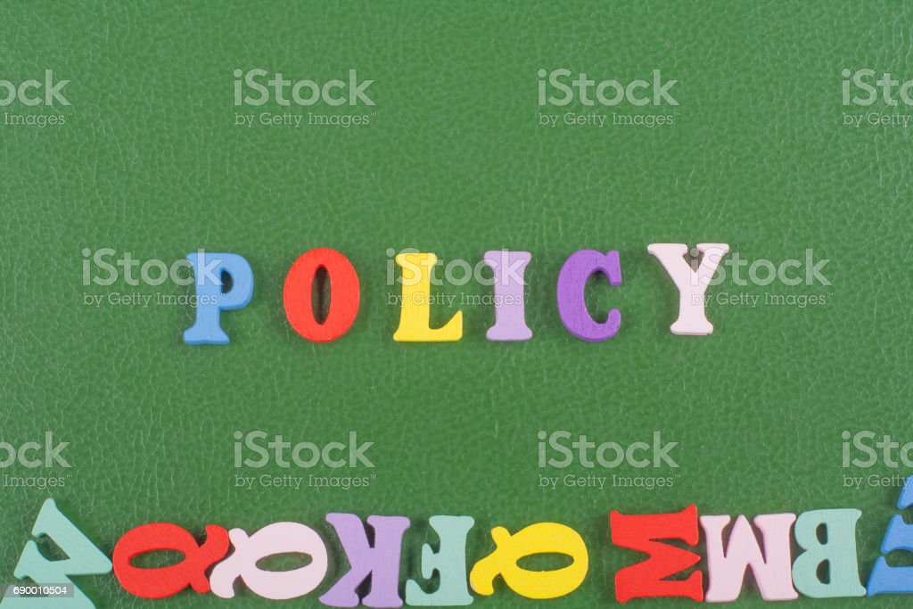 POLICY word on green background composed from colorful abc alphabet block wooden letters, copy space for ad text. Learning english concept stock photo