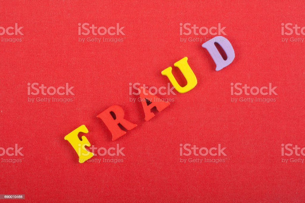 FRAUD word on red background composed from colorful abc alphabet block wooden letters, copy space for ad text. Learning english concept stock photo