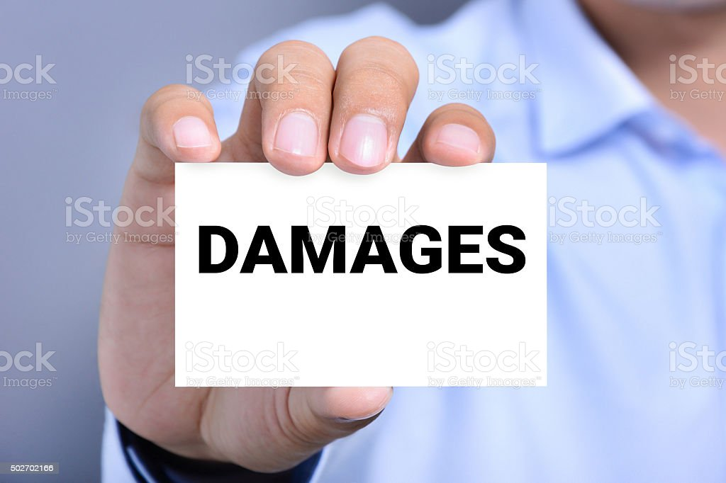 DAMAGES word on the card held by a man hand stock photo