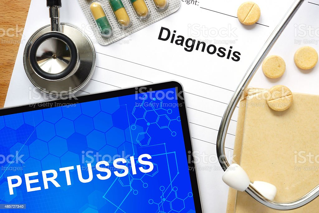 Word Pertussis on a book and pills. stock photo