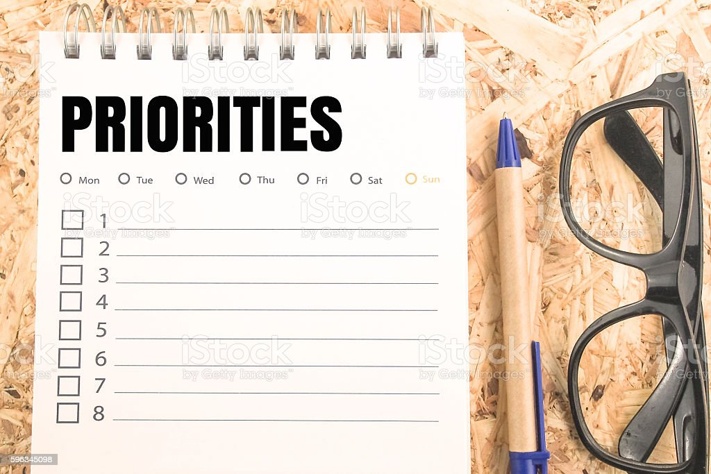 word prioritied check list on wooden table stock photo