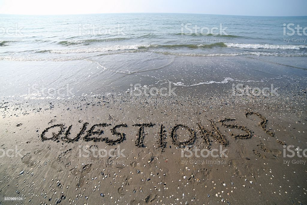 Word QUESTIONS written in large letters on the sand stock photo
