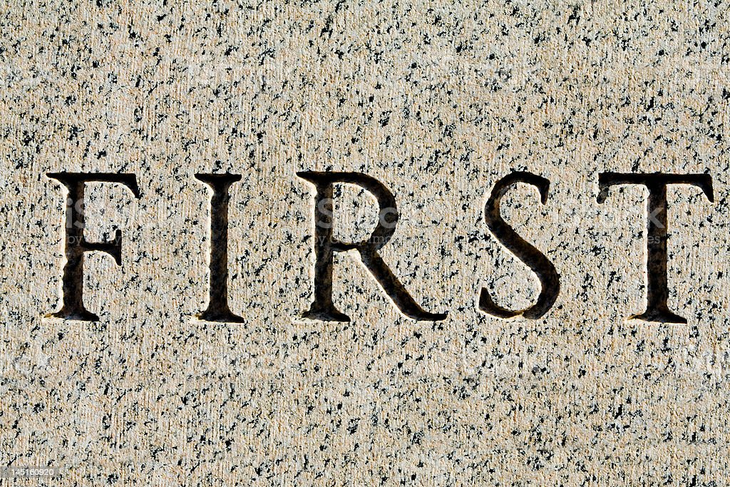 "Word ""First"" Carved in Gray Granite royalty-free stock photo"