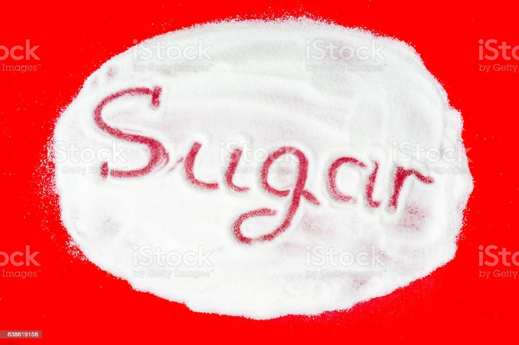 Word sugar written into a pile of white granulated sugar stock photo