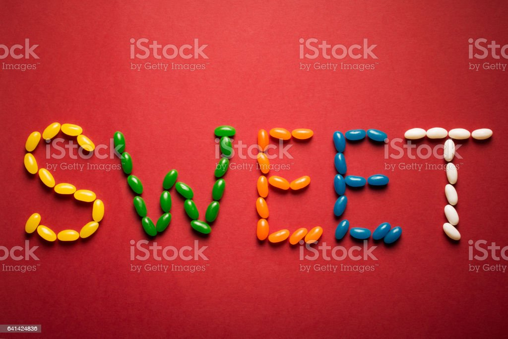 Word sweet from colorful candies on red background. Top view stock photo