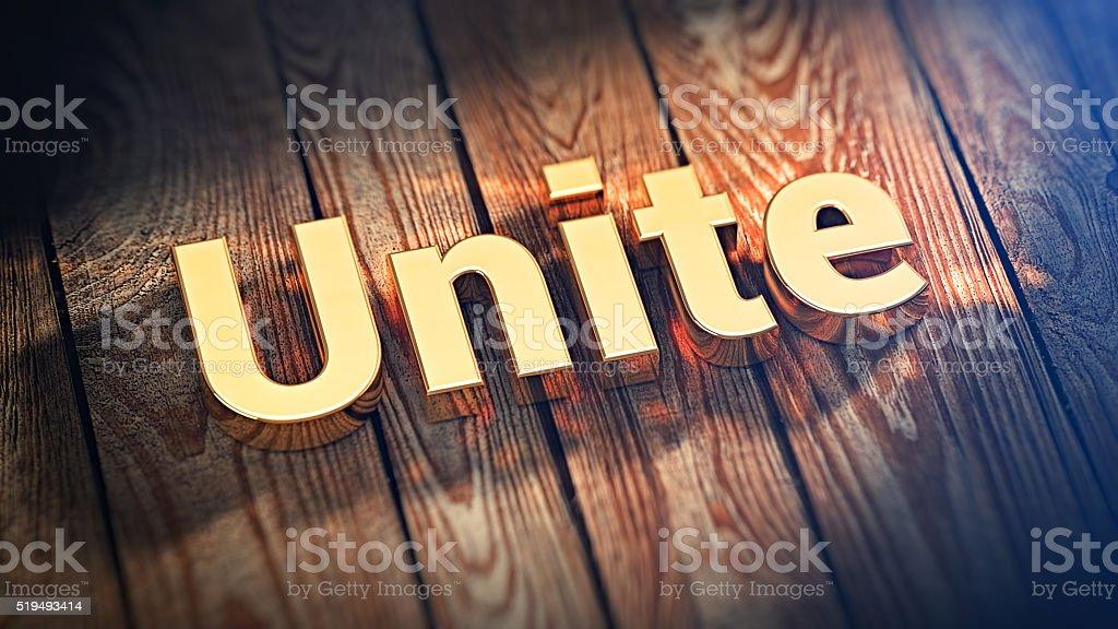Word Unite on wood planks stock photo