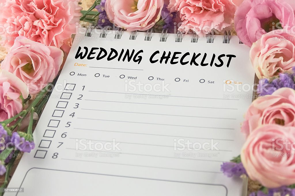 word wedding checklist note paper on pink flower background stock photo