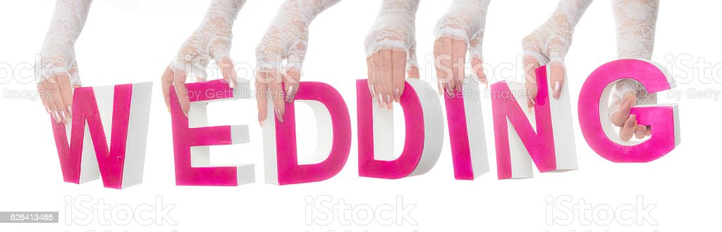 Word wedding hold up by bridal hands stock photo