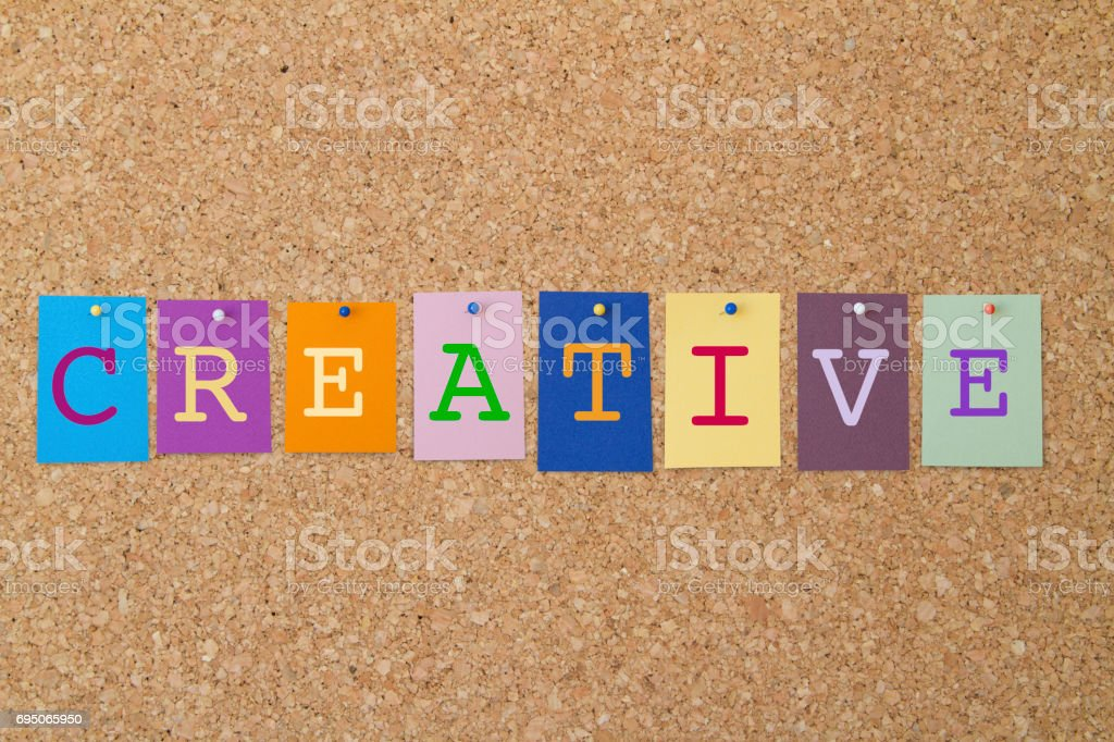 CREATIVE word written on colorful sticky notes pinned on cork board. stock photo