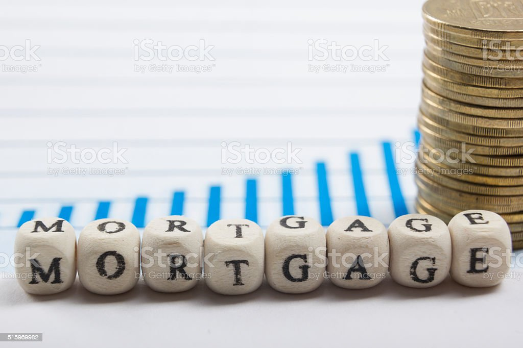 MORTGAGE word written on wood block, golden coins and chart stock photo