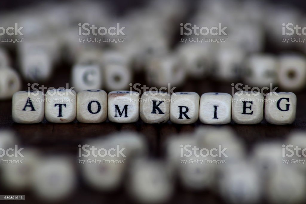 ATOMKRIEG word written on wood cube with dice background stock photo