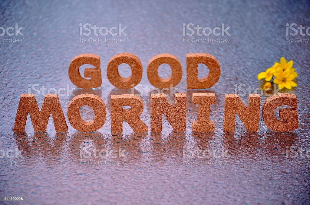 GOOD MORNING words and yellow flowers on wet background. stock photo