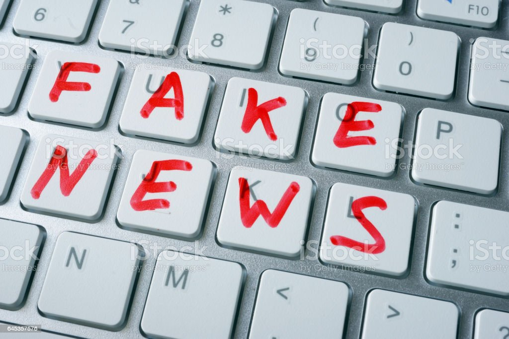 Words fake news written on a keyboard. stock photo